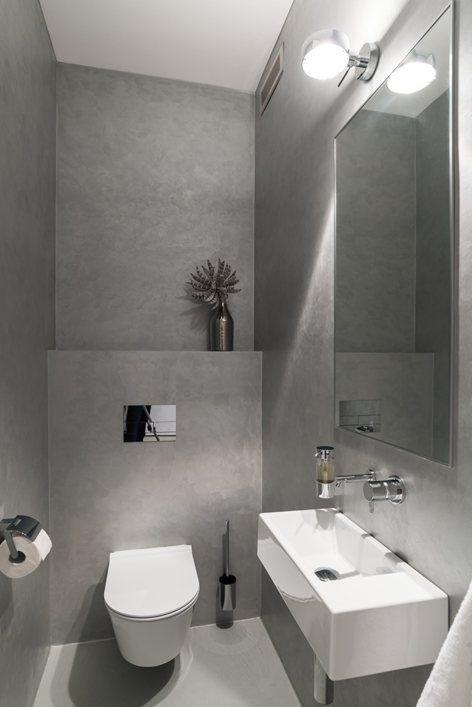 Vessan lattia ja seinät on pinnoitettu samalla harmaalla sävyllä. Pönttö ja käsienpesuallas ovat valkoset.