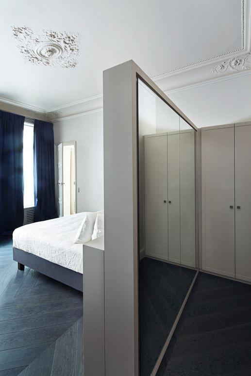 Makuuhuone on jaettu seinäkkeellä ja sijoitettu vaatehuone sängyn taakse.
