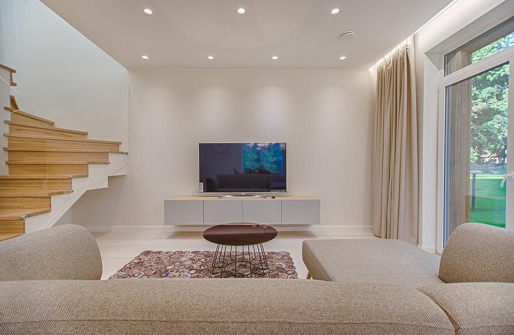 Modernissa yksinkertasessa olohuoneesa yhdistyy vaalean beigen väriset sävyt vitivalkoiseen vaaleanharmaaseen. Beige sohva ja verhot luovat lämpöä.