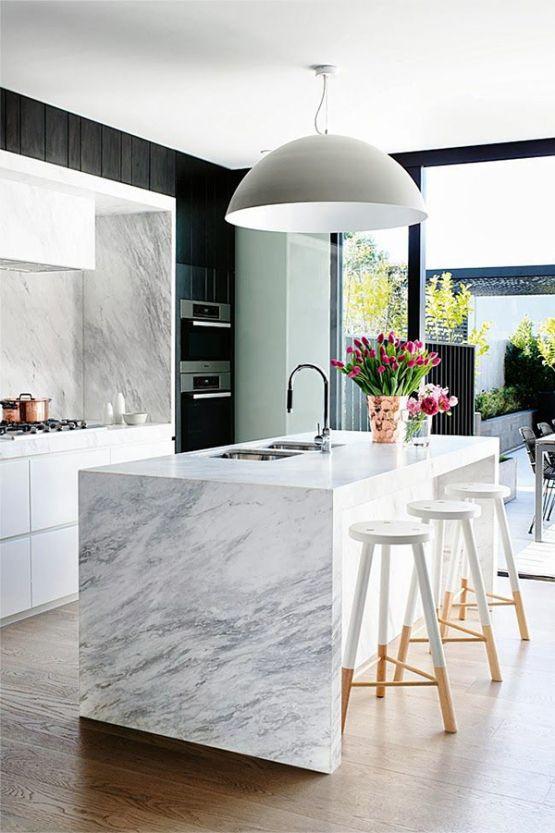 Modernissa keittiössä yhdistyy valkoiset alakaapit marmoriseen taustaseinään, joka on nostettu lähes kattoon asti. Saareke on kauttaaltaan samaa marmoria. Valkoisen keittiön raameina toimii mustat seinät.
