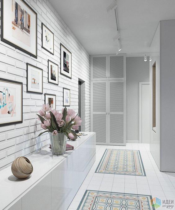 Valkoisen eteisen lattiaan on laatoitettu kaksi maton näköistä kuviota. Seinältä löytyy tiilikuvioinen tapetti, joka tuo vaihtelevuutta valkoisille pinnoille. Taulut on koottu samalla seinälle ryhmäksi ja pitkä matala valkoinen lipasto kätkee tavarat sisäänsä.