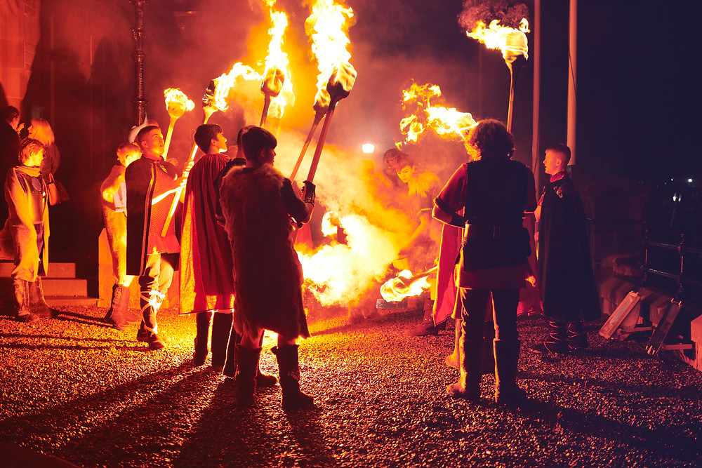 Young Men Mesmerized By Fire at Up Helly Aa.  Some of them lighting torches.  Some of them observing in awe. Picture use by permission of Visit Scotland via Zachary Burns