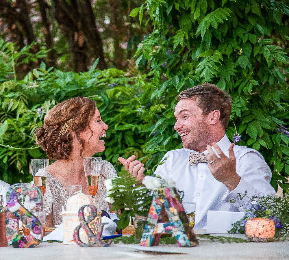 A lbride and groom laughing at each other in rural france