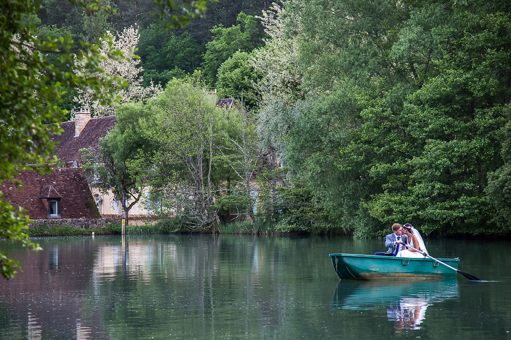 Couple in a boat on the lake at Forge du roy in Dordogne