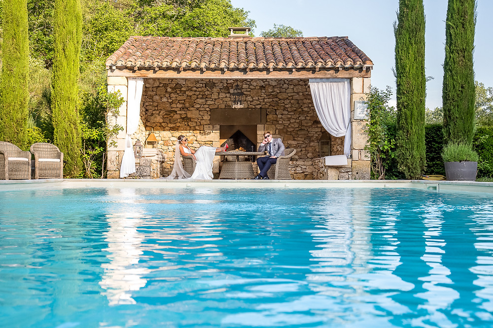 bride and groom sat round the pool at forge du roy
