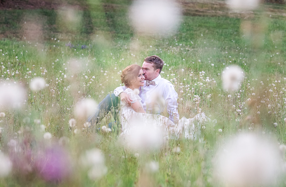 wedding couple relax in a pretty field