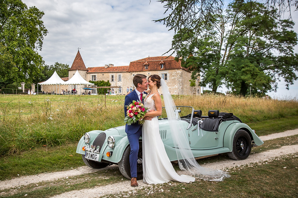 Bride and groom with vintage car infront of a chateau