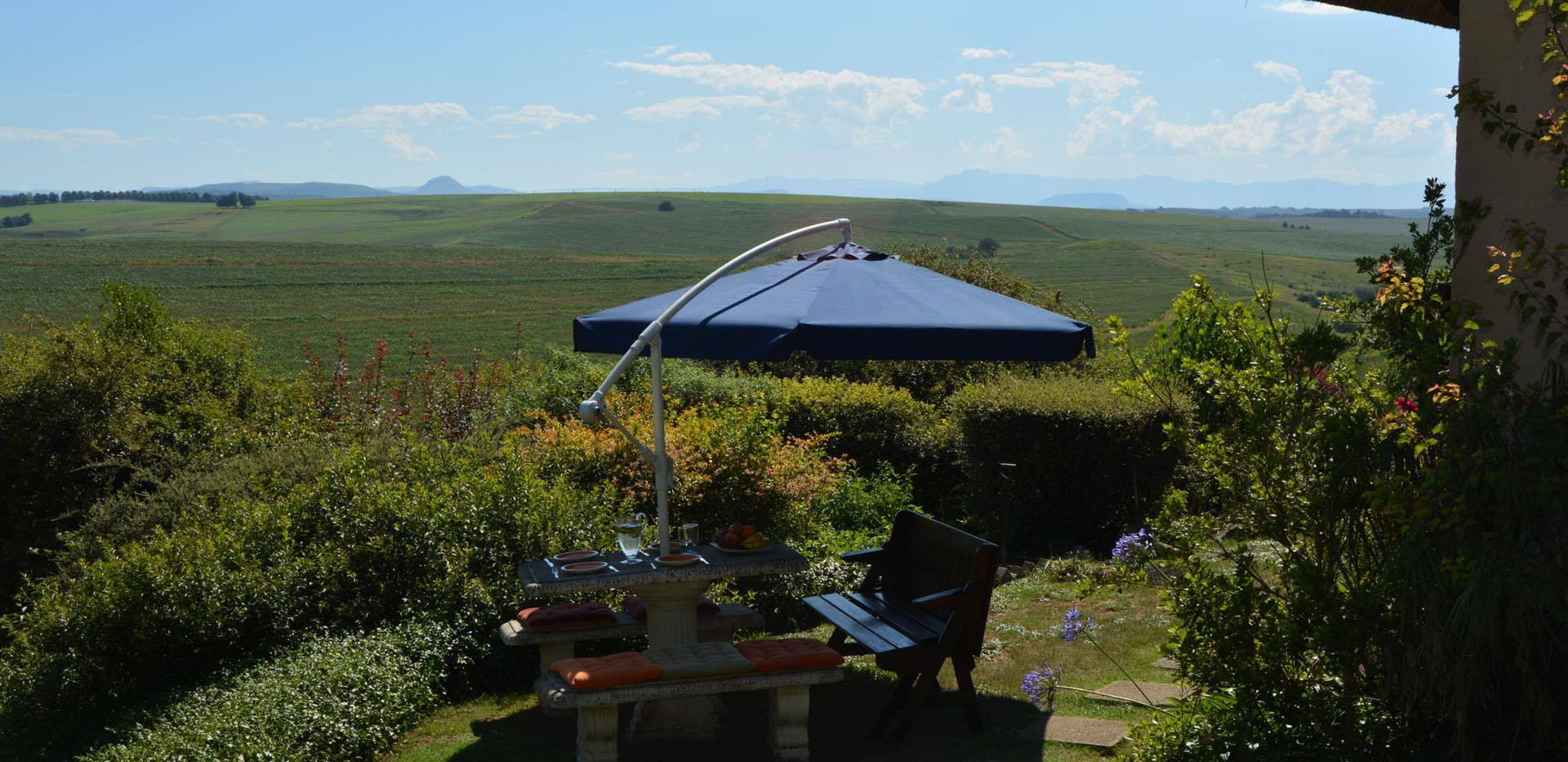 Garden with mountain view and outside seating area with unbrella