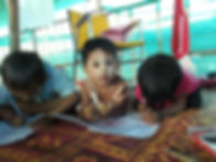 Burmese migrant students drawing pictures wearing thanaka