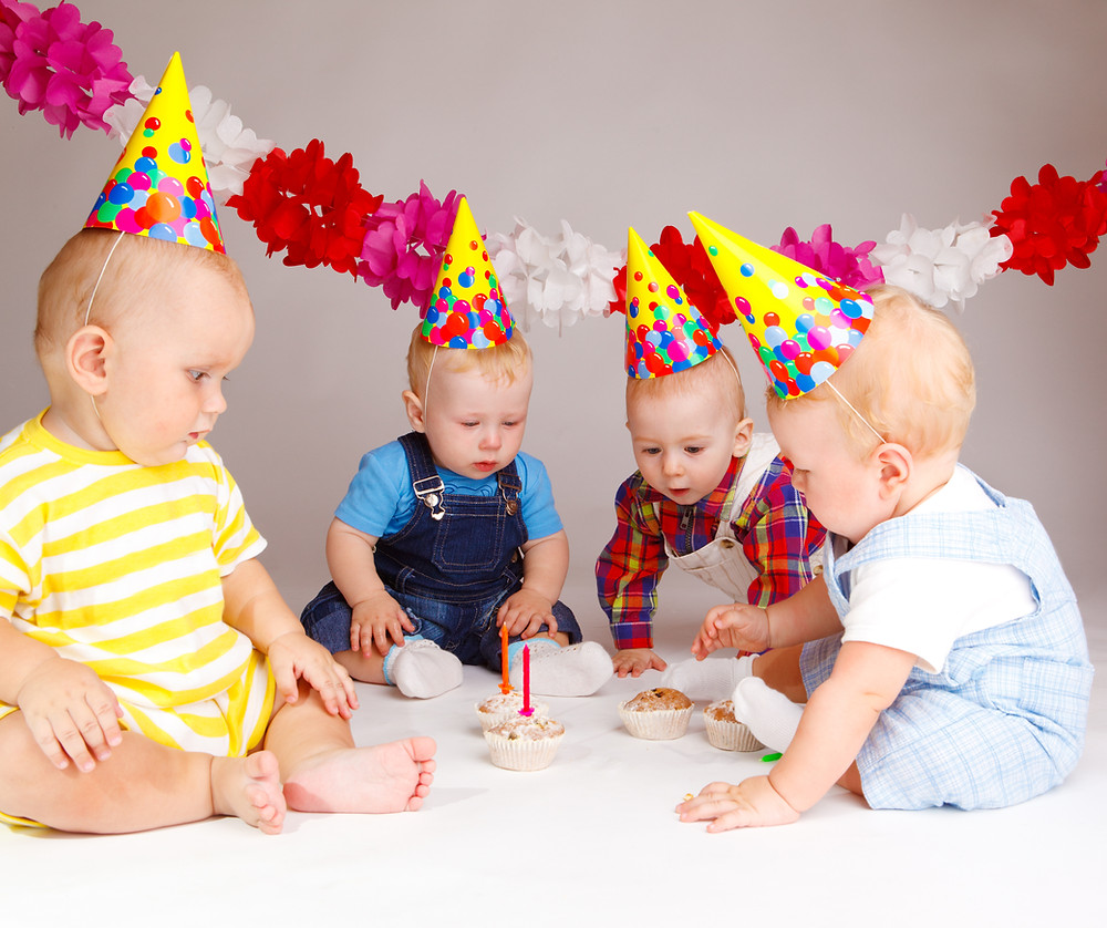 babies surrounding a birthday cake with decorations and one candle