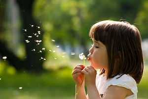 Beautiful child with dandelion flower in