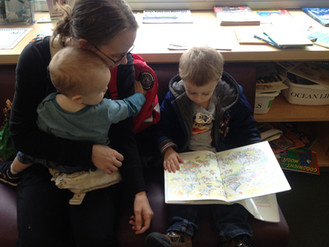 Mother reading to two young children