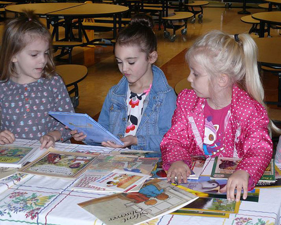 Three girls selecting books from a table