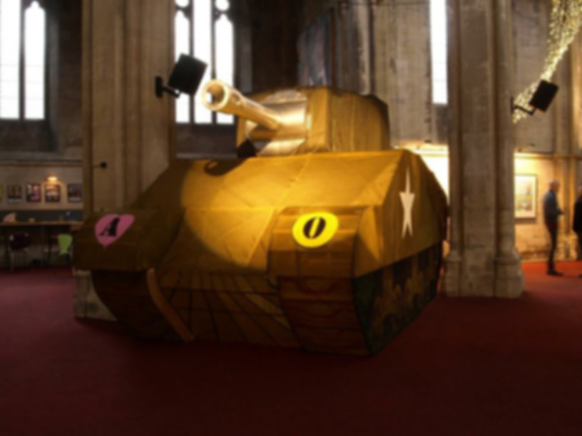 Large scale sculpture of Decoy Tank made with aluminium, wood and parachute material. Emblazoned with various symbols.