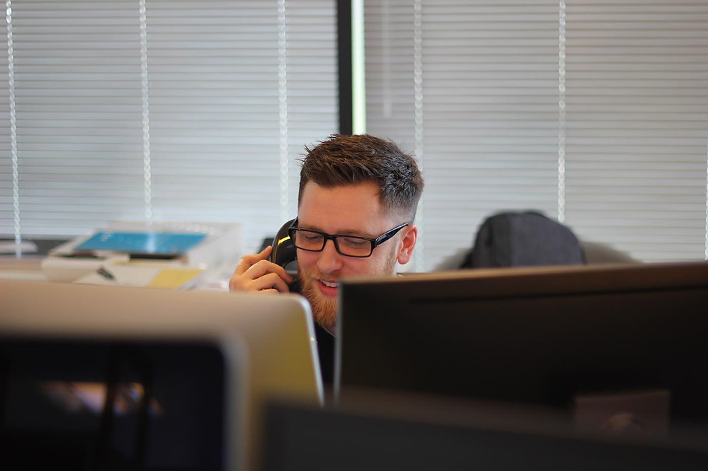 a man talking on the phone at his computer desk