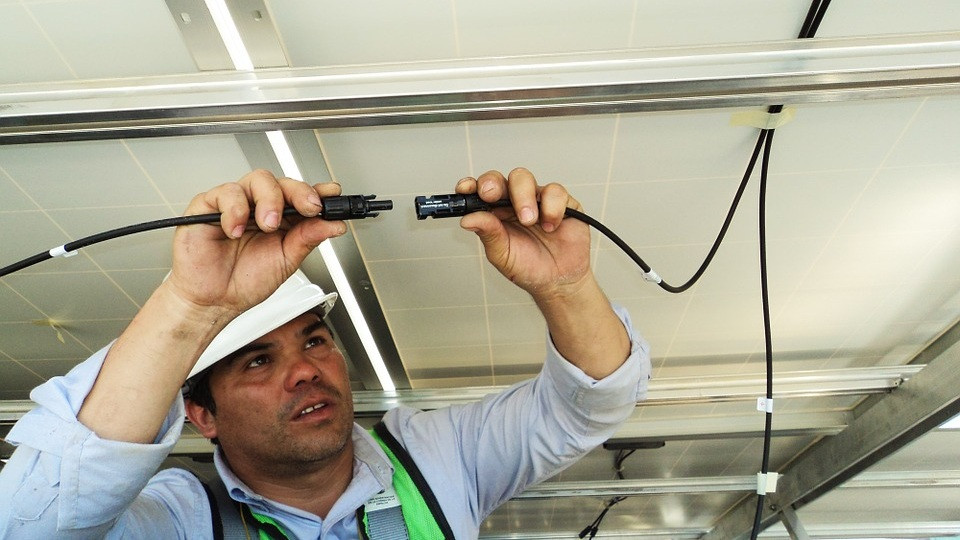 Solar PV technician linking a PV connector