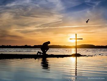 man-kneeling-prayer-cross-water.webp