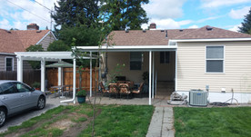 A solid patio cover attached at house with attaching pergola.