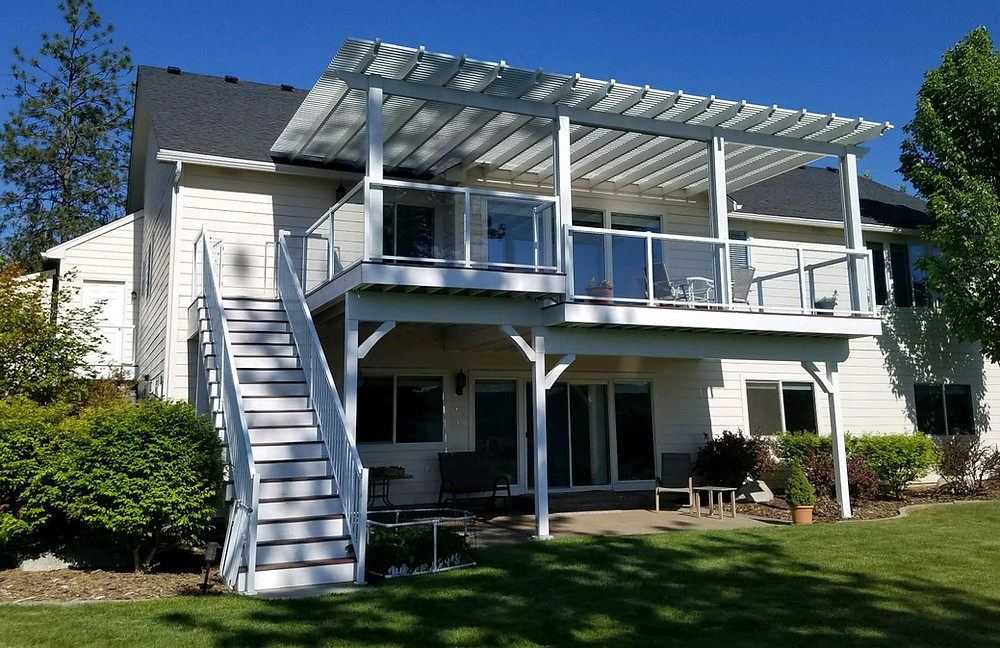 A pergola with glass railing around the deck and picket railing down the stairs. Is that not beautiful?