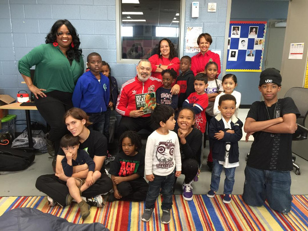 Students, volunteers, and teachers enjoying a celebrity reading