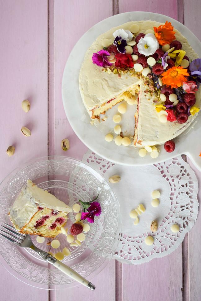 Queque de pistachos y frambuesas con frosting de chocolate blanco