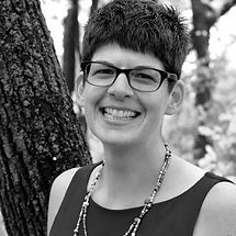 A black and white image of a Erin outdoors. She has short dark hair, glasses, and a long beaded necklace.