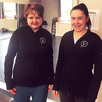 Two volunteers from Saturday morning classes face the camera. They are wearing their matching Dance On It Studios jackets.