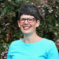 Erin smiles at the camera. She is a white woman with short dark brown hair. She wears thick rimmed square glasses and a turquoise t-shirt. The background is an out of focus bush with pink flowers