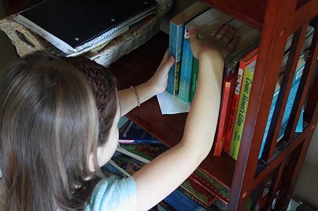 Child putting away book