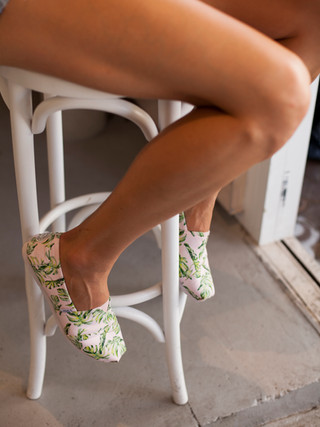 Legs sitting on stool in canvas shoes