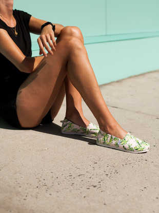Model sitting next to wall wearing shoes