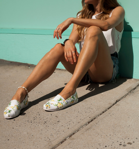 Model sitting next to a turquoise wall