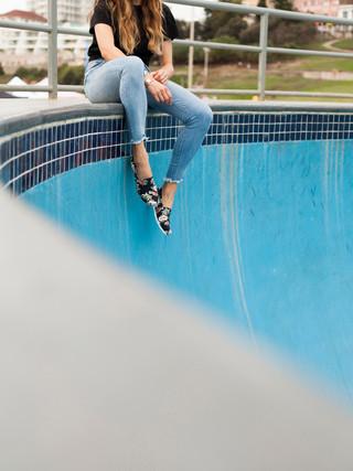 Model sitting in a skate park