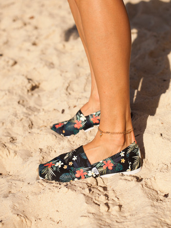 Model standing on sand in canvas shoes