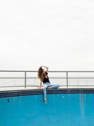Model sitting on edge of skate park