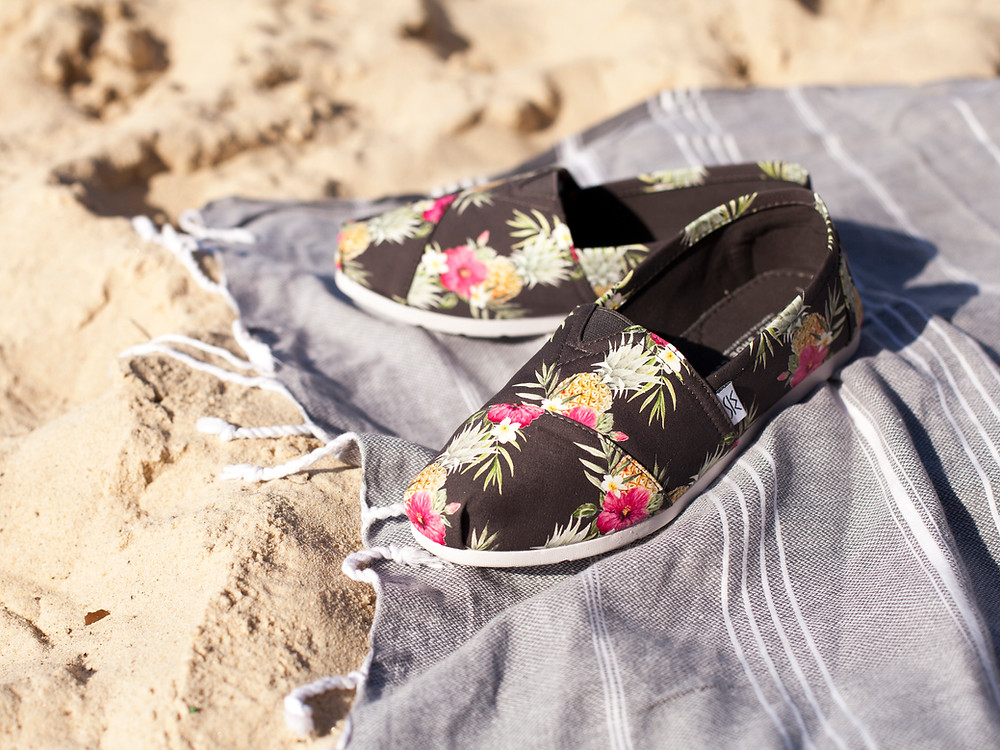 Pineapple print slip on canvas shoes on a beach