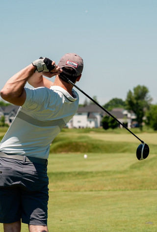 man in white t-shirt and black pants holding golf club during daytime_edited_edited.jpg