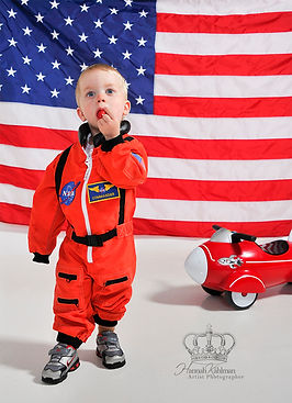 Boy_in_space_suit_infront_of_American_fl