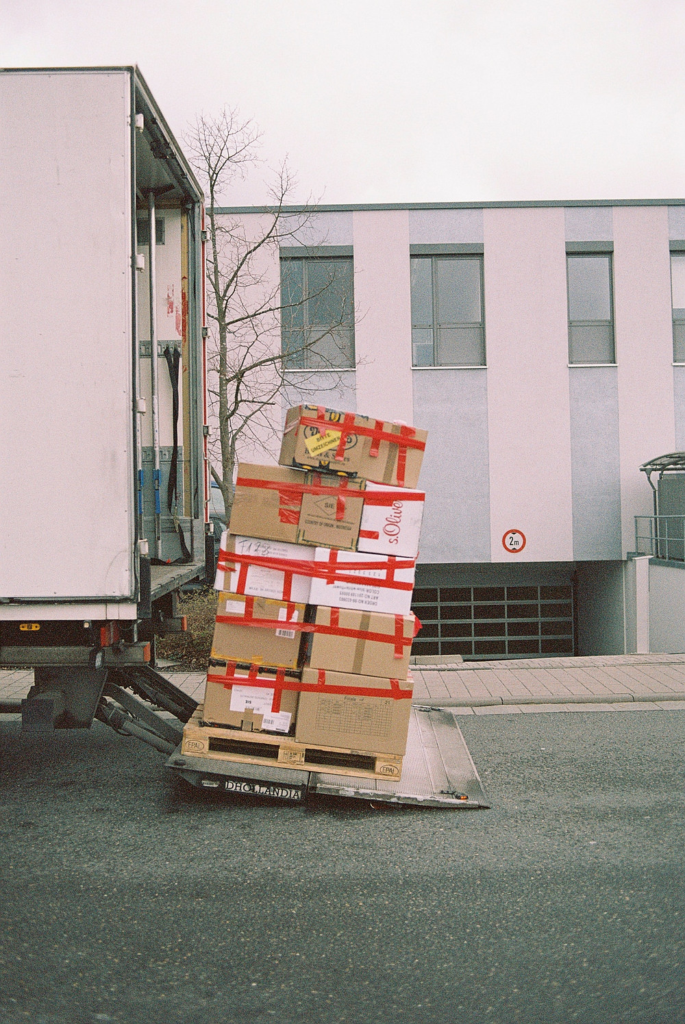 A crate of packages and boxes wrapped on the back of a lorry.