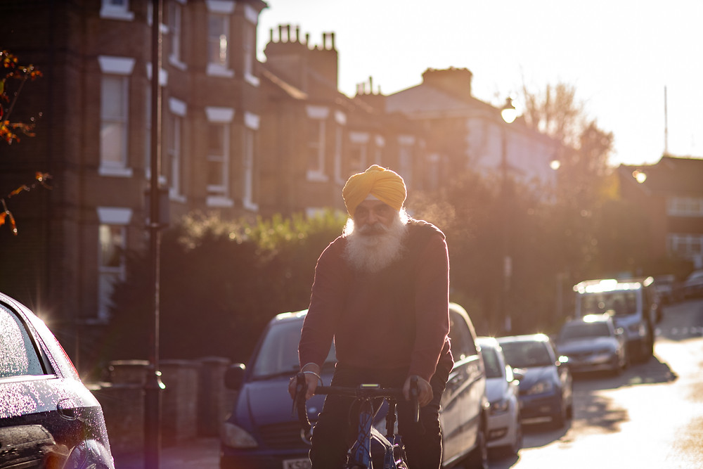 An older Sikh man riding a bicycle in a street