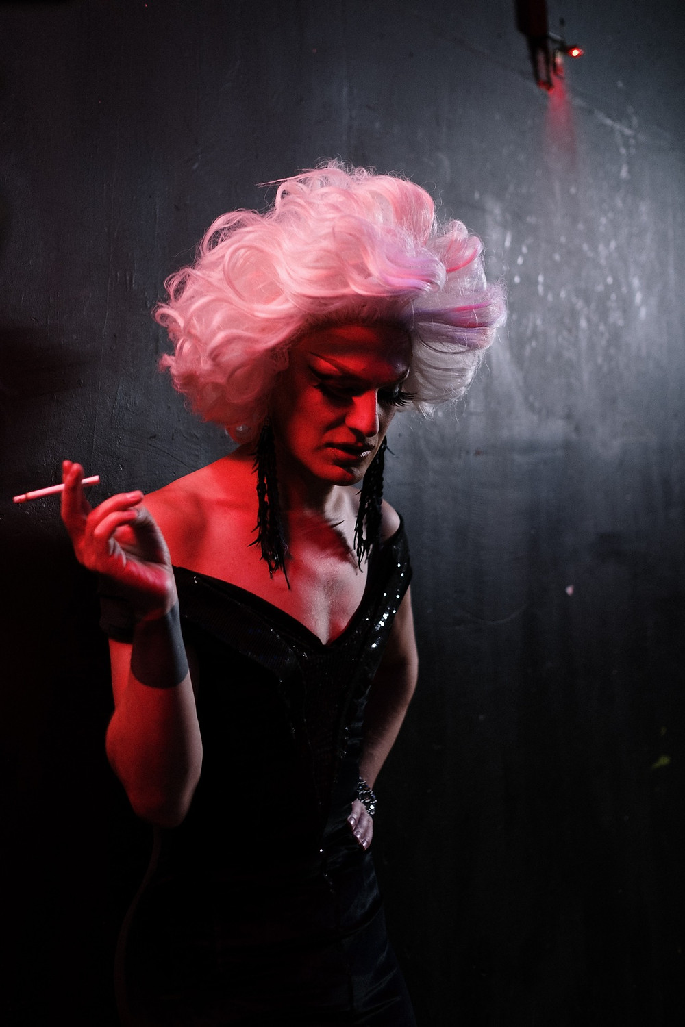 A drag queen with bright pink hair and long earrings smoking a cigarette with her hand on her hip wearing a black dress, lightly lit with a dark background.