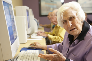 An old lady looking confused at a computer.