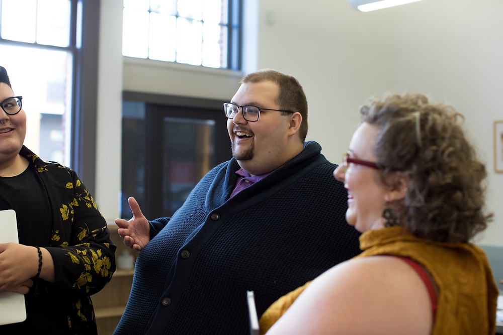three people are speaking to each other in an informal setting. They just happen to be plus-size people.