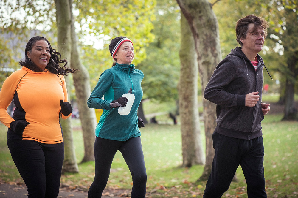 Three older people jogging in the woods.