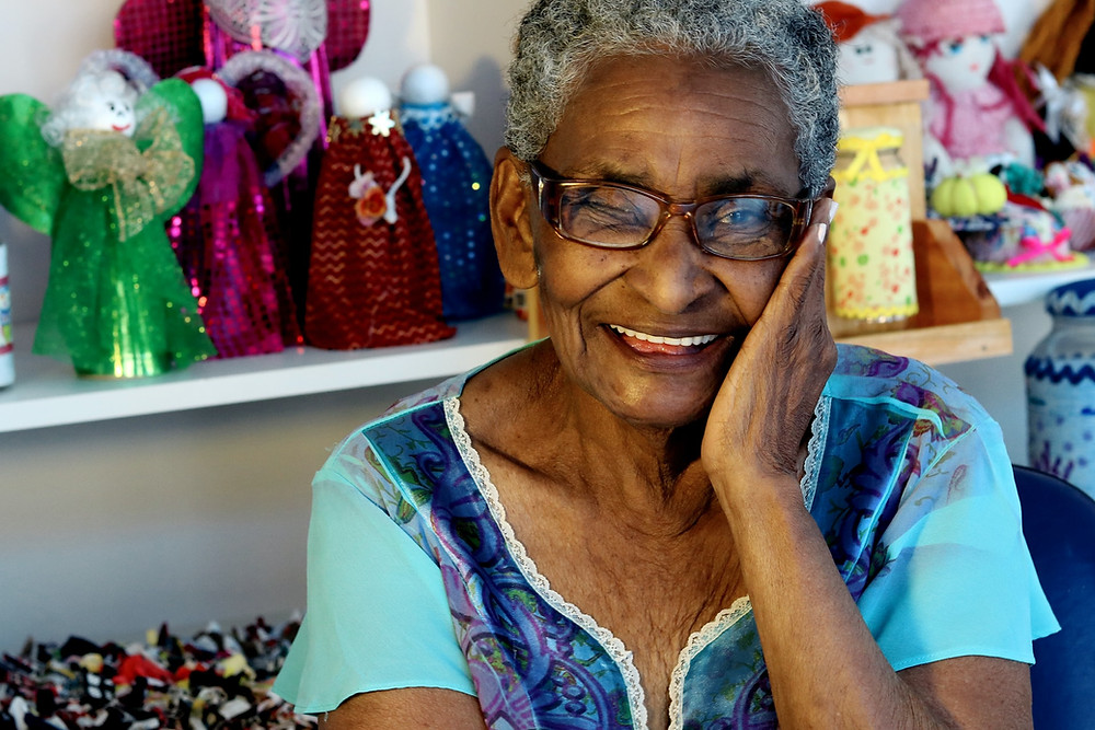 A black woman with grey hair and glasses wears a blue top. She is smiling at the camera and is resting her cheek on her hand. Behind her are multicoloured dolls on shelves.
