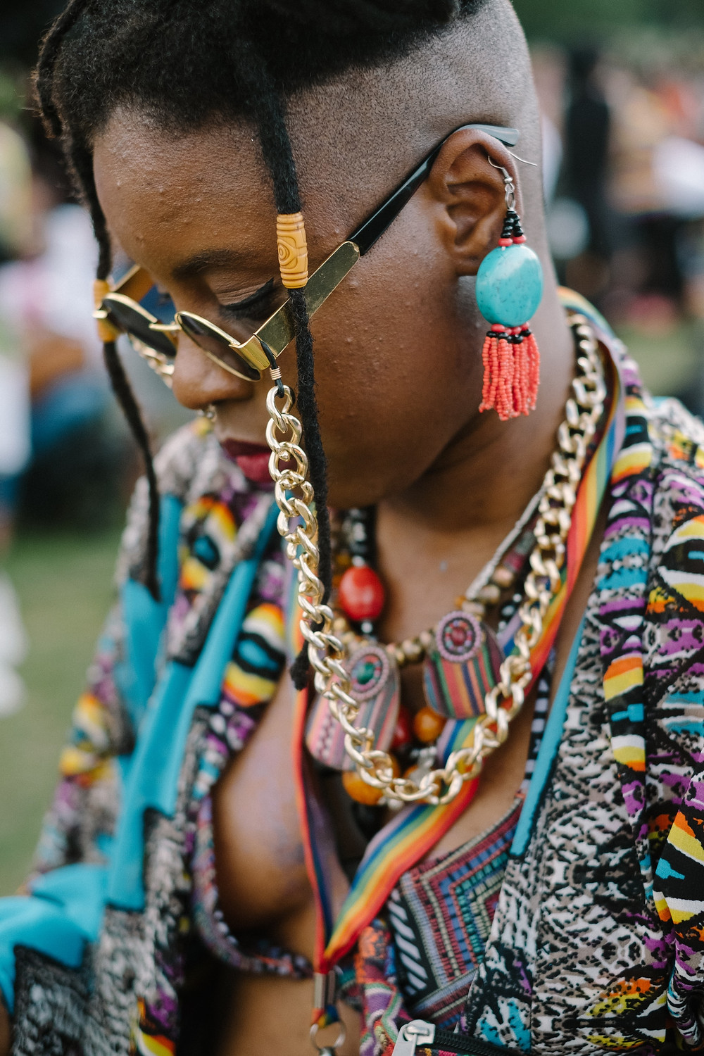 A black woman in close up with multiple pieces of jewellery, necklaces and earrings on. She is wearing sunglasses which are attached to large gold chains that go around her neck. She is wearing a multicoloured shirt and has two dreadlocks and a shaved head.