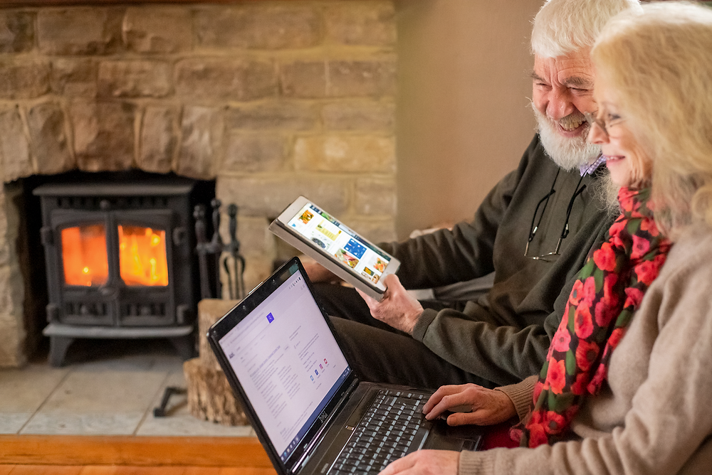 A older man and woman look at a laptop and tablet in front of a fireplace and log burner.