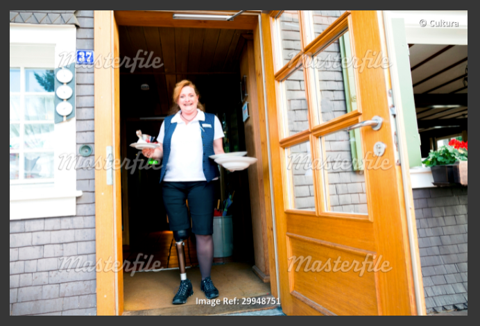 A female server is holding plates in a doorway of a cafe. She has a prosthetic leg.
