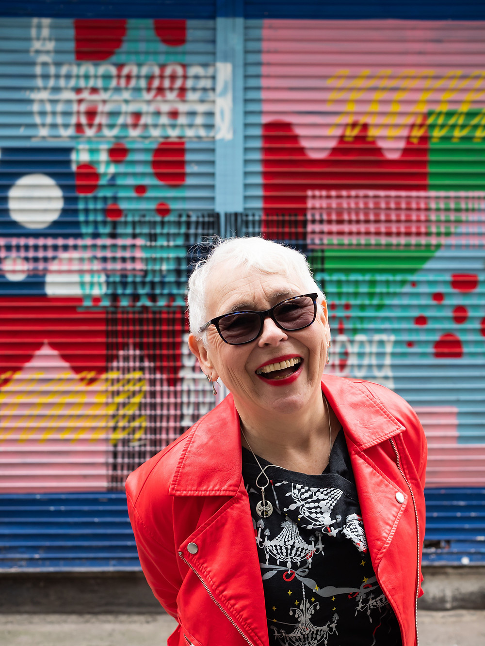 A woman with short, white hair is standing in front of a multicoloured and vibrant shop shutter. She is wearing a bright red, leather coat with a black top and sunglasses. She has a wide, happy smile.