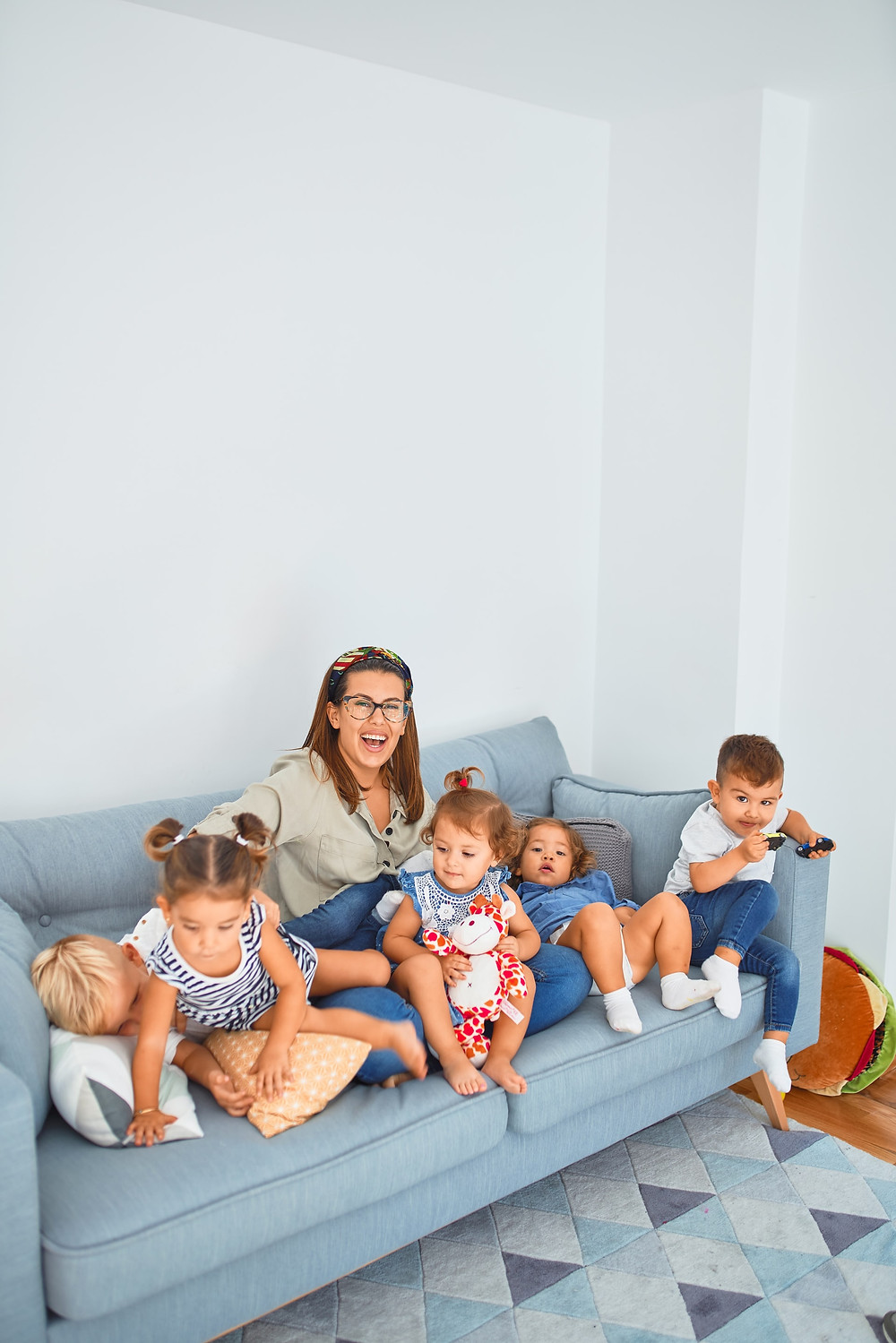 A woman with glasses sits on a light blue sofa with five toddlers around her. It seems there are three girls and two boys. It's possible that she is the children's mother, but it's also possible that she's not.